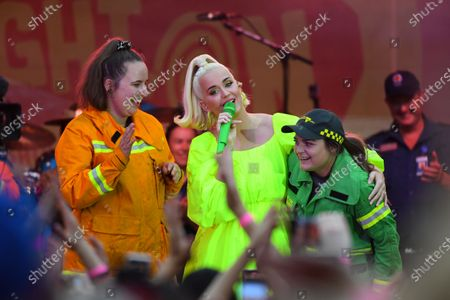 US singer Katy Perry (C) performs with a Country Fire Authority (CFA) and a Victorian Forest Fire Management employee during the 'FIGHT ON' concert for bushfire-affected communities at Pioneer Park Recreation Reserve in Bright, Victoria, Australia, 11 March 2020. The pop star is putting on a free show in Victoria's Alpine region.
