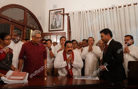 Stock Photo of Sri Lankan Prime Minister Mahinda Rajapaksa, center, greets the gathering as he prepares to sign election nomination papers for his candidacy in the upcoming parliamentary elections, as his brother, Sri Lankan President Gotabhaya Rajapaksa, left in red shirt, and former president Maithripala Sirisena, third right, watch in Colombo, Sri Lanka, . Sri Lanka will go for parliamentary polls in April