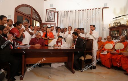 Sri Lankan Prime Minister Mahinda Rajapaksa, wearing red scarf, signs election nomination papers for his candidacy in the upcoming parliamentary elections, as his brother and Sri Lankan President Gotabhaya Rajapaksa, center left in red shirt, and former president Maithripala Sirisena, standing third right, watch in Colombo, Sri Lanka, . Sri Lanka will go for parliamentary polls in April