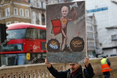 Satirical artist Kaya Mar holds up a painting showing the picture of political advisor Dominic Cummings who works for Prime Minister bBoris Johnson outside Downing Street in London, . Britain's Chancellor of the Exchequer Rishi Sunak will announce the first budget since Britain left the European Union