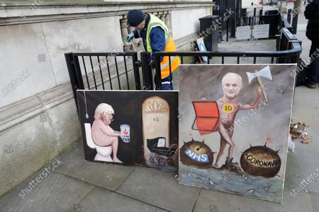 Works by Satirical artist Kaya Mar are displayed by a railing outside Downing Street of political advisor Dominic Cummings, right and Britain's Prime Minister Boris Johnson, in London, . Britain's Chancellor of the Exchequer Rishi Sunak will announce the first budget since Britain left the European Union