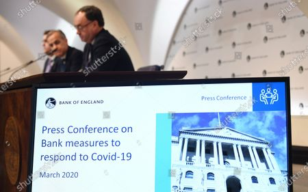 A screen displays information about an emergency press conference held by Bank of England Governor Mark Carney (C, back) in London, Britain, 11 March 2020. The Bank of England has announced it has cut interest rates in response to the Coronavirus outbreak.