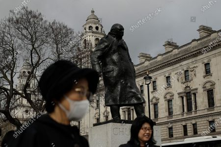 Tourist was a mask to help avoid getting coronavirus as she stands next to the statue of former British Prime Minister Winston Churchill in Parliament Square in London, . A British government minister Nadine Dorries, who is a junior Heath minster has tested positive for the coronavirus and is self isolating