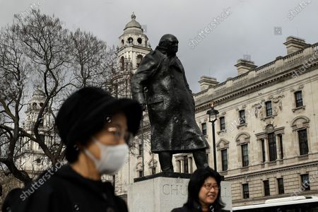 Tourist was a mask to help avoid getting coronavirus as she stands next to the statue of former British Prime Minister Winston Churchill in Parliament Square in London, . A British government minister Nadine Dorries, who is a junior Heath minster has tested positive for the coronavirus and is self isolating. For most people, the new coronavirus causes only mild or moderate symptoms, such as fever and cough. For some, especially older adults and people with existing health problems, it can cause more severe illness, including pneumonia
