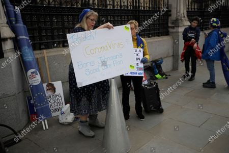Anti Brexit campaigners hold placards including comments on the outbreak of coronavirus as they protest outside Parliament in London, . A British government minister Nadine Dorries, who is a junior Heath minster has tested positive for the coronavirus and is self isolating. Britain's Chancellor of the Exchequer Rishi Sunak will announce the first budget since Britain left the European Union