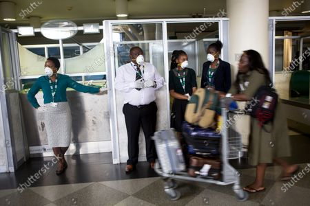 Travellers and airport staff, some wearing masks, walk through Robert Mugabe International airport in Harare, Wednesday, March, 11, 2020. For most people, the new coronavirus causes only mild or moderate symptoms, such as fever and cough. For some, especially older adults and people with existing health problems, it can cause more severe illness, including pneumonia