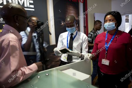 Traveller has his passport checked by staff wearing masks at Robert Mugabe International airport in Harare, Wednesday, March, 11, 2020. For most people, the new coronavirus causes only mild or moderate symptoms, such as fever and cough. For some, especially older adults and people with existing health problems, it can cause more severe illness, including pneumonia