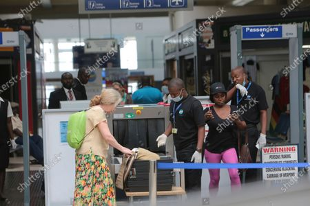 Travellers and airport staff, some wearing masks, walk through Robert Mugabe International airport in Harare, Wednesday, March, 11, 2020. For most people, the new coronavirus causes only mild or moderate symptoms such as fever and cough. For some, especially older adults and people with existing health problems, it can cause more severe illness, including pneumonia