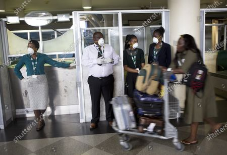 Travellers and airport staff, some wearing masks as a precaution against the coronavirus outbreak, walk through Robert Mugabe International airport in Harare, Wednesday, March, 11, 2020. For most people, the new coronavirus causes only mild or moderate symptoms, such as fever and cough. For some, especially older adults and people with existing health problems, it can cause more severe illness, including pneumonia
