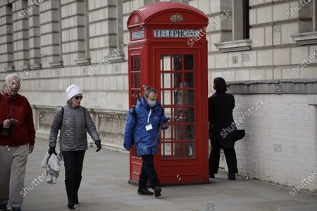 Man wearing a face mask walks past a traditional British red phone box near Parliament Square in central London, . A British government minister Nadine Dorries, who is a junior Heath minster has tested positive for the coronavirus and is self isolating. For most people, the new coronavirus causes only mild or moderate symptoms, such as fever and cough. For some, especially older adults and people with existing health problems, it can cause more severe illness, including pneumonia