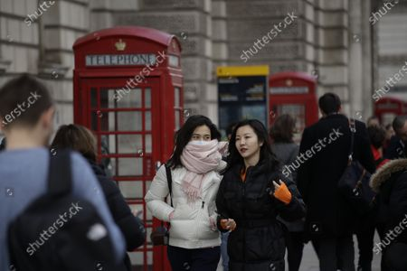 Woman wearing a scarf covering a face mask walks past traditional British red phone boxes near Parliament Square in central London, . A British government minister Nadine Dorries, who is a junior Heath minster has tested positive for the coronavirus and is self isolating. For most people, the new coronavirus causes only mild or moderate symptoms, such as fever and cough. For some, especially older adults and people with existing health problems, it can cause more severe illness, including pneumonia