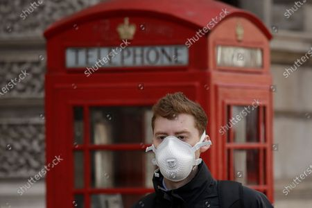 Man wearing a face mask walks past a traditional British red phone box just off Parliament Square in central London, . A British government minister Nadine Dorries, who is a junior Heath minster has tested positive for the coronavirus and is self isolating. For most people, the new coronavirus causes only mild or moderate symptoms, such as fever and cough. For some, especially older adults and people with existing health problems, it can cause more severe illness, including pneumonia
