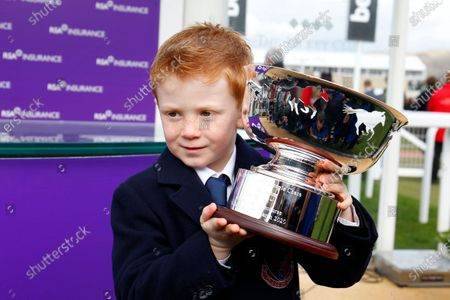 Archie McCoy son of Sir AP McCoy with the winning trophy after Champ had won the RSA Chase at Cheltenham.