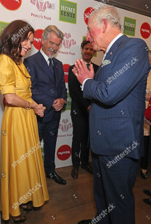 Prince Charles greets Anna Friel and Pierce Brosnan with a Namaste gesture as he arrives at the annual Prince's Trust Awards 2020 held at the London Palladium