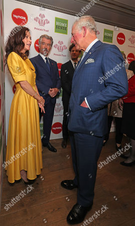 Prince Charles greets Anna Friel and Pierce Brosnan as he arrives at the annual Prince's Trust Awards 2020 held at the London Palladium