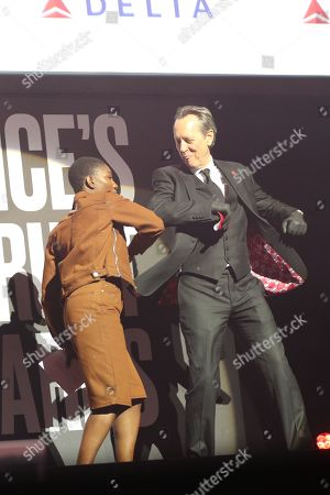 Michaela Coel and Richard E Grant greet each other with an elbow bump on stage at the annual Prince's Trust Awards 2020 held at the London Palladium