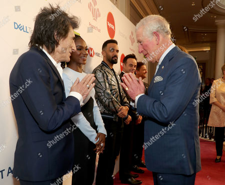 Prince Charles uses a Namaste gesture to greet Rolling Stone Ronnie Wood as he arrives at the annual Prince's Trust Awards 2020 held at the London Palladium