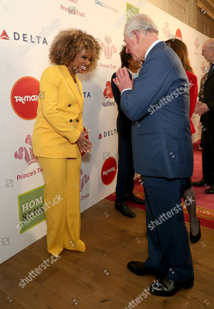 Prince Charles uses the Namaste gesture to greet Fleur East as he arrives at the annual Prince's Trust Awards 2020 held at the London Palladium