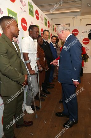 Prince Charles speaks with actors Michael Ward and Ashley Walters (left) as he arrives at the annual Prince's Trust Awards 2020 held at the London Palladium