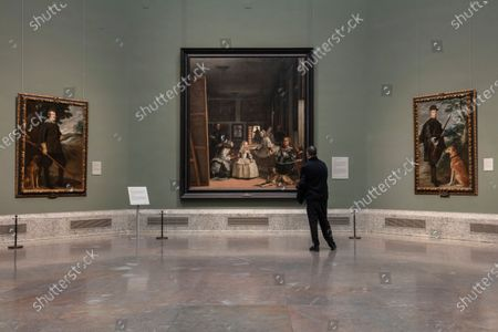 Visitor looks at 'Las Meninas' by Diego Velazquez at El Prado museum in Madrid, Spain, . On Tuesday, the Spanish health ministry imposed safety measures on areas most afected by COVID-19, including a ban on indoor gatherings for more than 1,000 people. For most people, the new coronavirus causes only mild or moderate symptoms, such as fever and cough. For some, especially older adults and people with existing health problems, it can cause more severe illness, including pneumonia