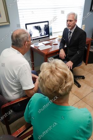 Dr. Mitchell Supler, right, has a discussion with Mike and Susan McNally at the Masson Spine Institute in Ocoee, Fla. The McNallys first used a UnitedHealthcare navigator when Mike was preparing for shoulder surgery a few years ago. Navigator Kimberly Eklond intervened. She contacted the hospital and told the Florida couple they didn't have to pay anything early and could actually make no-interest payments after the procedure
