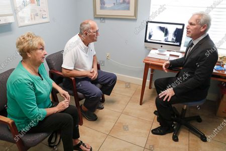 Dr. Mitchell Supler, right, has a discussion with Susan and Mike McNally at the Masson Spine Institute in Ocoee, Fla. The McNallys first used a UnitedHealthcare navigator when Mike was preparing for shoulder surgery a few years ago. Navigator Kimberly Eklond intervened. She contacted the hospital and told the Florida couple they didn't have to pay anything early and could actually make no-interest payments after the procedure