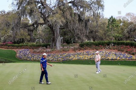 Hideki Matsuyama of Japan (L) walks across the thirteenth green as Branden Grace of South Africa (R) prepares to putt during practice for THE PLAYERS Championship on the Stadium Course at TPC Sawgrass in Ponte Vedra Beach, Florida, USA, 11 March 2020. The contest will run from 12 to 15 March.