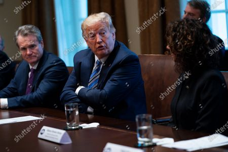 Bank of America CEO Brian Moynihan, left, and CEO of the Independent Community Bankers of America Rebeca Romero Rainey, right, listen as President Donald Trump speaks during a meeting with banking industry executives about the coronavirus, at the White House, in Washington