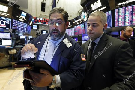 Director of Trading Floor Operations Fernando Munoz, right, works with trader Robert Oswald, on the floor of the New York Stock Exchange, . Stocks are closing sharply lower on Wall Street, erasing more than 1,400 points from the Dow industrials, as investors wait for a more aggressive response from the U.S. government to economic fallout from the coronavirus. For most people, the new coronavirus causes only mild or moderate symptoms. For some it can cause more severe illness