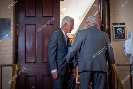 Rep. Charlie Crist, D-Fla., center, pauses to speak with Rep. Gerry Connolly, D-Va., right, in the doorway to a closed House Democratic caucus meeting called by Speaker of the House Nancy Pelosi, D-Calif., as she moves toward House passage of a coronavirus aid package possibly this week, on Capitol Hill in Washington