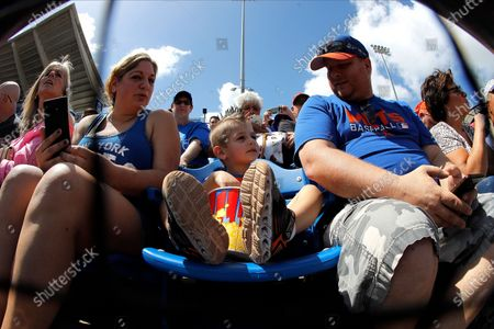 Austin Abrams, 4, of Newburg, N.Y., sits with his parents while watching the first inning of a spring training baseball game between the St. Louis Cardinals and the New York Mets, in Port S. Lucie, Fla