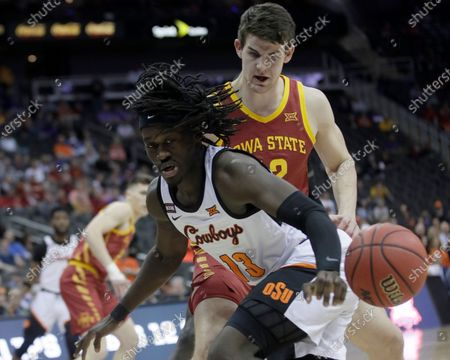 Oklahoma State guard Isaac Likekele (13) and Iowa State forward Michael Jacobson (12) chase a loose ball during the first half of an NCAA college basketball game in the first round of the Big 12 men's basketball tournament in Kansas City, Kan