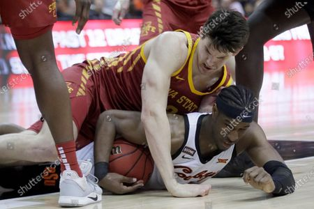 Stock Photo of Iowa State forward Michael Jacobson, top, and Oklahoma State forward Cameron McGriff, bottom, hit the floor after the ball during the first half of an NCAA college basketball game in the first round of the Big 12 men's basketball tournament in Kansas City, Kan