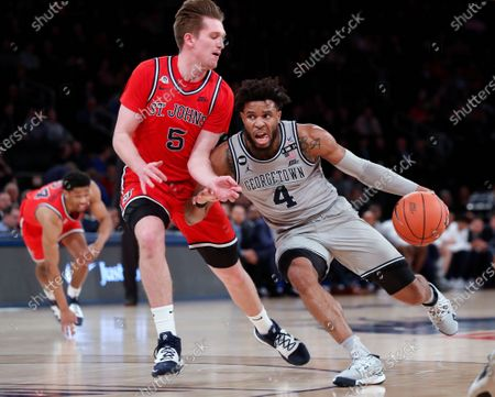 Georgetown guard Jagan Mosely (4) drives around St. John's guard Greg Williams Jr. (4) during the first half of an NCAA college basketball game in the first round of the Big East men's tournament, in New York