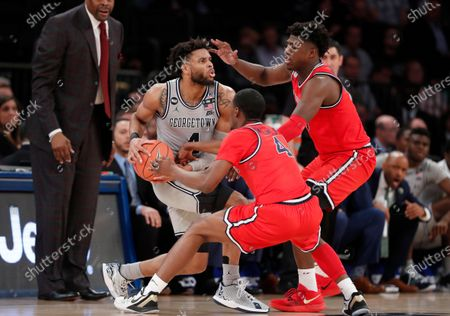 St. John's guard Greg Williams Jr., middle, and forward Marcellus Earlington (10) defend against Georgetown guard Jagan Mosely, left, during the second half of an NCAA college basketball game in the first round of the Big East men's tournament, in New York
