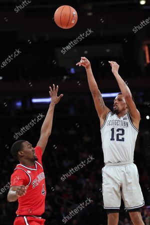 St. John's guard Greg Williams Jr. (4) defends as Georgetown guard Terrell Allen (12) shoots during the first half of an NCAA college basketball game in the first round of the Big East men's tournament, in New York
