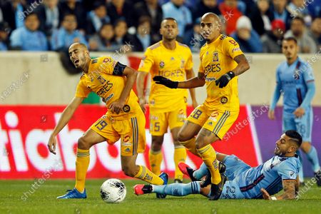 Tigres midfielder Guido Pizarro (19) reacts as he is tripped by New York City FC defender Ronald Matarrita (22) behind Tigres midfielder Luis Rodríguez (28) during the first half in the first leg of a quarterfinal in the CONCACAF Champions League soccer tournament, in Harrison, N.J