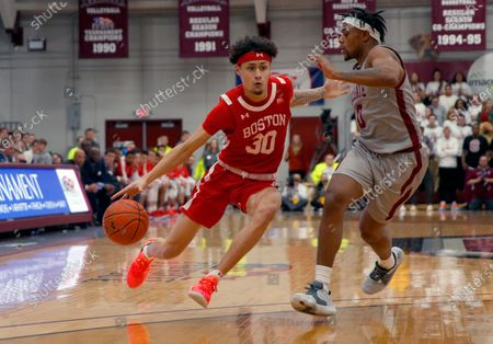 Boston University's Javante McCoy (30) drives past Colgate's Nelly Cummings (0) during the first half of the NCAA Patriot League Conference college basketball championship at Cotterell Court, in Hamilton, N.Y