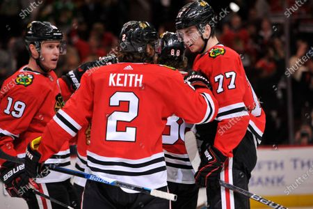 Chicago Blackhawks' Duncan Keith (2) celebrates with teammates Kirby Dach (77) and Jonathan Toews (19) after scoring a goal during the second period of an NHL hockey game against the San Jose Sharks, in Chicago