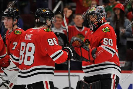 Chicago Blackhawks goalie Corey Crawford (50) celebrates with Patrick Kane (88) after the Blackhawks defeated the San Jose Sharks 6-2 in an NHL hockey game, in Chicago