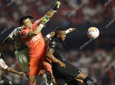 Luis Antonio Valencia of Ecuador's Liga Deportiva Universitaria, right, jumps for a header as goalkeeper Tiago Volpi of Brazil's Sao Paulo defends, during a Copa Libertadores soccer match in Sao Paulo, Brazil