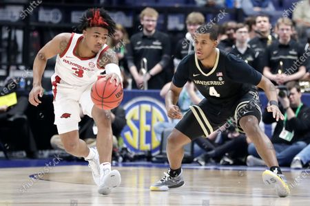 Arkansas guard Desi Sills (3) is defended by Vanderbilt's Jordan Wright (4) in the first half of an NCAA college basketball game in the Southeastern Conference Tournament, in Nashville, Tenn