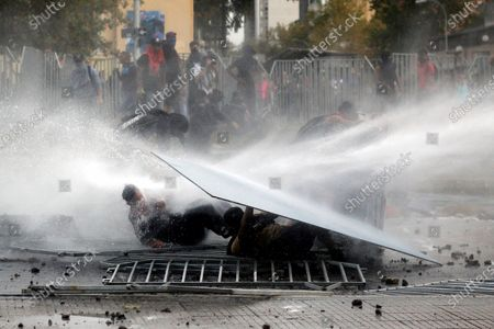 Protesters are hit by a water jet from a riot police vehicle during protests commemorating the two years of the government of Sebastian Pinera, in Santiago, Chile, 11 March 2020.