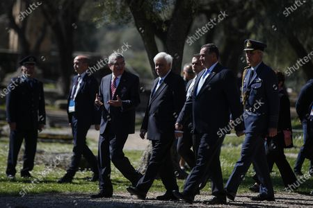 Head of the Hellenic Olympic committee Spyros Kapralos, second right, Greek President Prokopis Pavlopoulos, second left, and IOC President Thomas Bach, left, arrive to the flame lighting ceremony at the closed Ancient Olympia site, birthplace of the ancient Olympics in southern Greece, . Greek Olympic officials are holding a pared-down flame-lighting ceremony for the Tokyo Games due to concerns over the spread of the coronavirus. Both Wednesday's dress rehearsal and Thursday's lighting ceremony will be closed to the public, while organizers have slashed the number of officials from the International Olympic Committee and the Tokyo Organizing Committee, as well as journalists at the flame-lighting