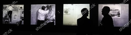 Two people walk in front of a video-installation by South African artist William Kentridge during its presentation at Guggenheim Bilbao Museum, in Bilbao, Basque Country, northern Spain, 12 March 2020. The artwork is dedicated to cinema pioneer George Melies.