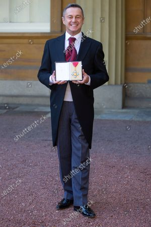 Stock Picture of Stephen Mear proudly displays his CBE for services to dance following his investiture