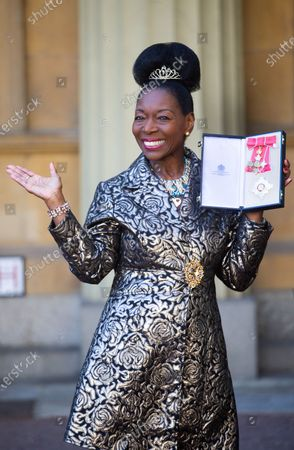 Baroness Floella Benjamin poses with her Dame Commander award for services to charity, following her investiture