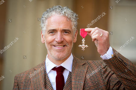 Stock Image of Gordon Buchanan with his MBE medal, awarded at an investiture ceremony at Buckingham Palace