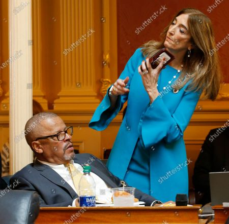 House speaker Del. Eileen Filler-Corn, right, prepares to make a call after talking with House Appropriations committee chairman, Del. Luke Torian, D-Prince William, during a break in the House session at the Capitol Thursday March 12, 2020, in Richmond, Va
