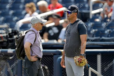 Brian Cashman, left, general manager of the New York Yankees, talks with manager Aaron Boone prior to a spring training baseball game against the Washington Nationals, in West Palm Beach, Fla